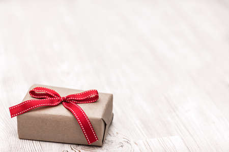 Christmas present with red ribbon bow laid on a wooden table background 版權商用圖片