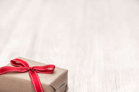 Vintage gift box (package) with red ribbon bow laid on a wooden background 版權商用圖片