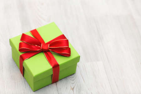 Green gift box with red ribbon bow laid on a wooden background. Top view Christmas background 版權商用圖片