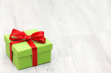 Christmas green gift box with red ribbon bow laid on a wooden background. Top view Christmas background