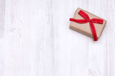 Christmas gift box with red ribbon bow laid on a wooden background