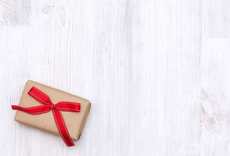 Wrapped vintage gift box with red ribbon bow laid on a wooden background. Top view Christmas background 版權商用圖片