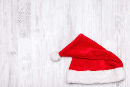 Santa Claus hat on wooden background. Top view.