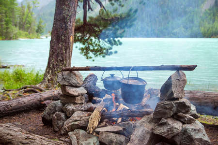 Camp in the mountains near of the lake. Cooking a meal on a campfire