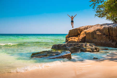 The happy young man jumping off cliff into the ocean. Summer fun, lifestyle, extreme sport. 版權商用圖片