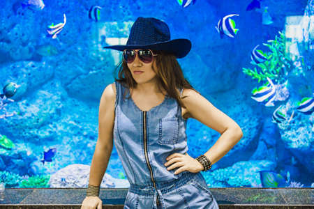 Woman in the background blue aquarium. Beautiful female model with copy space.
