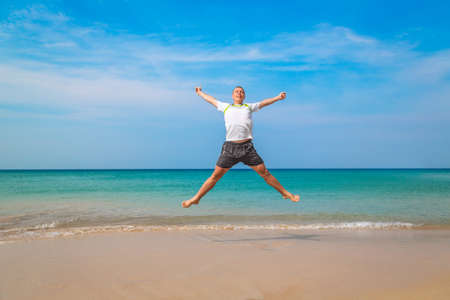 Happy tourist man jumping in a tropical beach. Travel concept and vacations 版權商用圖片