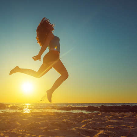 Freedom, lifestyle and holiday concept. Happy woman jumping on the beach against beautiful yellow sunset. 版權商用圖片