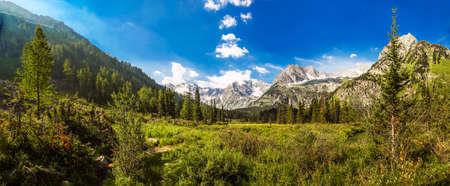 Mountain peak range landscape with high rocky peaks. Green mountain range view. Blue sky panorama.