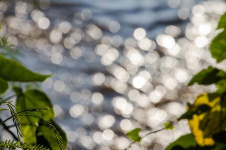 Bokeh komt uit de zon als achtergrond op het water. focus lens vervagen.