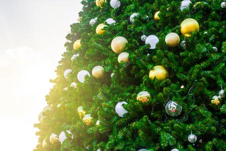 Christmas tree decorated with gold balls and mirror balls background.