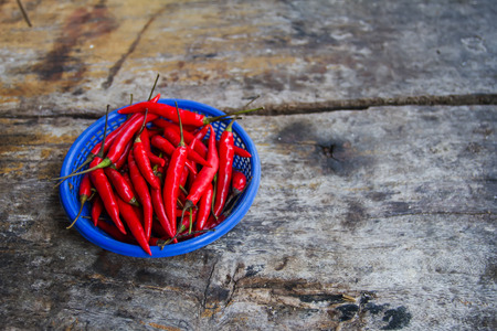 Fresh chili in cooking spicy by them provided in a basket placed on the wooden floor. Imagens