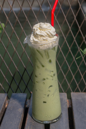 Iced green tea with whipped cream set on table ready to serve.