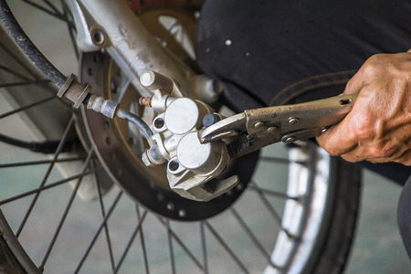 Technician are change disk brakes for motorcycle Zdjęcie Seryjne - 110121973