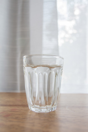 Glass of water placed on a table can be used to decorate. Zdjęcie Seryjne