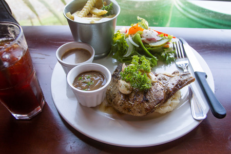 The main dish is the pork chop Were placed on a table ready to be served. Zdjęcie Seryjne
