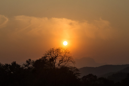 View images of the sun falling behind the mountains. 写真素材