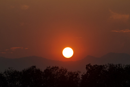View of the sun setting down behind the mountains.