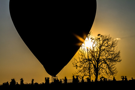 silhouette balloon floating in the air, the sun in the evening. 写真素材