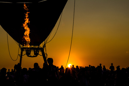 Image of the evening sun with the flaming silhouette with balloon is being. 写真素材