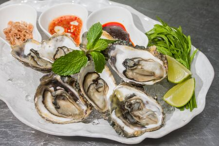 The oysters were placed on a plate with ice and side dishes. Zdjęcie Seryjne - 149649736