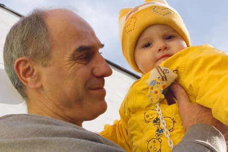 Grandfather holds his granddaughter in hands against the blue sky photo