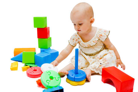 Little baby girl playing with her toys, isolated on white photo