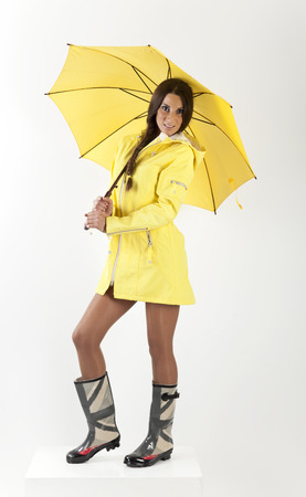 rain coat: young girl in a yellow raincoat and rubber boots Stock Photo