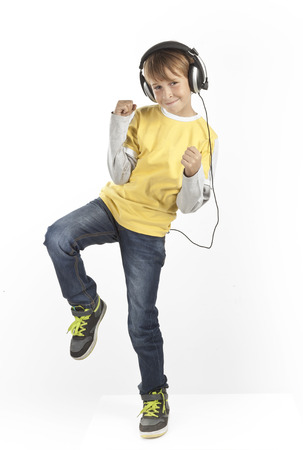 boy with headphones dancing on white background