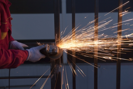Worker cutting metal with grinder photo