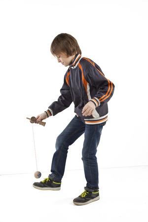 young boy playing kendama isolated