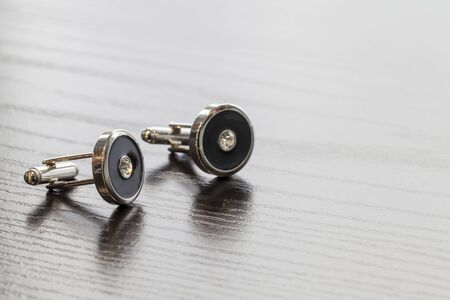silver cuff links on wooden table colse up photo