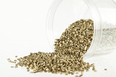 granules: gold plastic granules close up