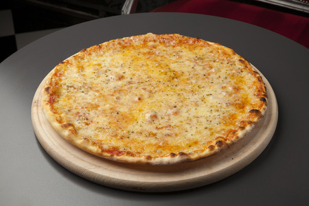 Pizza on wooden board with mozzarella