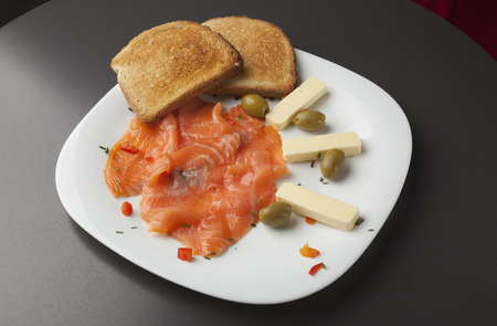 filets: Smoked salmon filets with toasted bread and olives on white plate Stock Photo