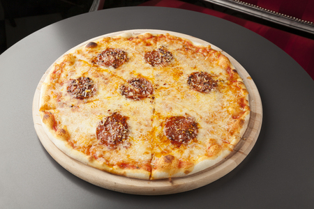 pepperoni: pepperoni pizza with sausage on wooden plate Stock Photo