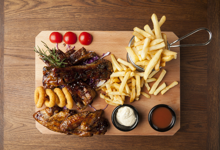 meat grill: chicken wings and ribs with fries on wooden table Stock Photo