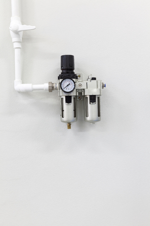 compressed air hose: pressure regulator with a pressure gauge on white wall