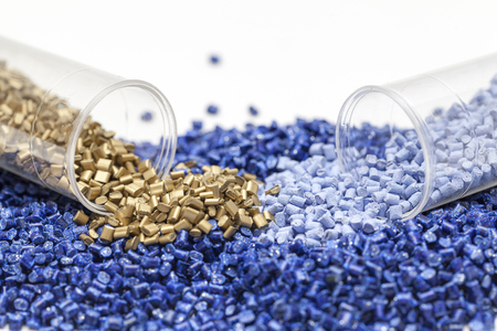 plastic granules, blue and gold close up Stock Photo