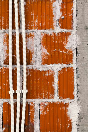 plastered brick wall with plastic corrugated tubes for the electrical installation Stock Photo