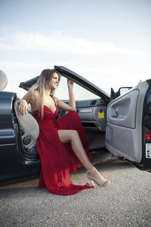 beside: girl in a red dress posing beside convertible Stock Photo