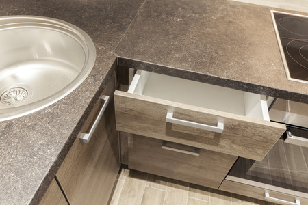 kitchen cabinets: kitchen counter with sink and drawers open