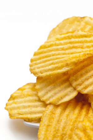 Ribbed potato chips with spices on white background