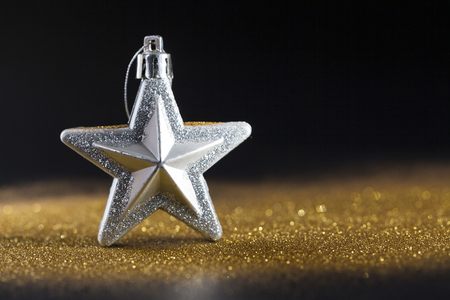 golden sparkles with silver star on black background, christmas card