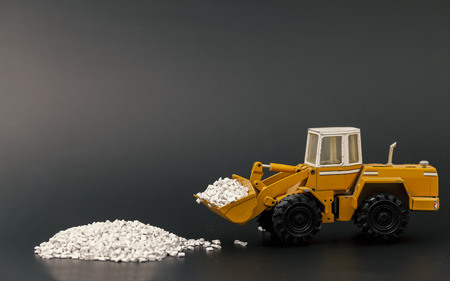 toy bulldozer moving plastic granules on black background