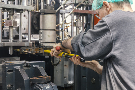 worker repairs a machine for plastic injection, close up