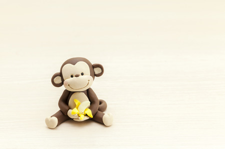 Little monkey toy sitting with a banana, marzipan decorations Stock Photo