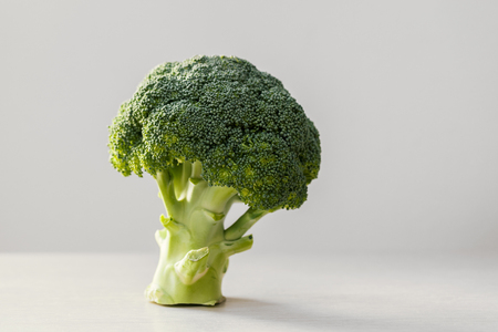 one fresh broccoli on wooden plate, close up