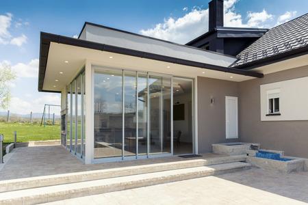 verglaste Terrasse im Grünen mit Schiebeverglasung Standard-Bild