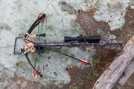 hunting crossbow with an arrow and optical sight on concrete